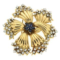 This stylish Valentin Magro brooch is made in 18kt yellow gold, it features pear shape and round blue SAPPHIRES in the center of the brooch. 2.80 carat total weight of round brilliant diamonds are set with VVS clarity and D.E.F color. Circa 2004