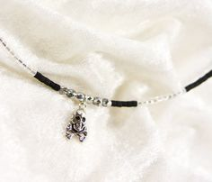 No bones about it. This black and silver memory wire necklace with a one-sided sterling silver skull-and-crossbones charm is as tough as it is feminine. Matte jet and clear seed beads are punctuated by half-silver fire-polished Czech glass. Lightweight and sturdy enough for everyday. $20 via Etsy. Get 15% off your entire SmallestPlanet purchase with coupon code PIN15.