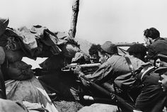 SPAIN. Members of the Republican army using a Vikers machine gun fabricated in England. 1936