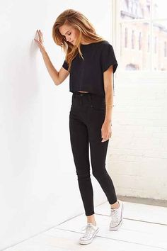 Yep, simplicity is the key, darling. Go for totally black outfit, like this one, what consists of shortened semi-sheer tee, high-rise skinnies and cool white trainers.