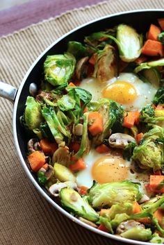 Stir up a hearty sweet potato hash with brussels sprouts and mushrooms. Eggs nestled in the vegetables bring protein to a tasty, power-packed meal, perfect for a Whole 30.