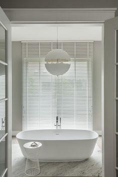 freistehende Badewanne in Weiß und hängende Designer leuchte