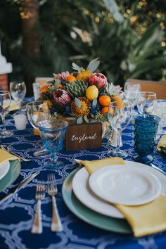 Mediterranean Inspired Wedding Reception Round Table Decor with Low Yellow, Orange, Red and Succulent Greenery Centerpiece with Lemons and Persimmon, Wooden Table Number European Country Names Sign with White Script, Sage Green Chargers and Yellow Napkins, Cobalt Blue Patterned Tablecloth, and Blue Painted China Plates   Sarasota Wedding Planner Jennifer Matteo Event Planning   Over the Top Rental Linens