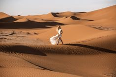girl in wedding dress walking on sand dunes Caitlin Hartley of It Girl Weddings http://itgirlweddings.com/desert-editorial-shoot/