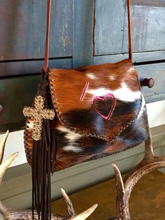 The Going Downtown bag. Lined in chocolate brown suede, with the owners brand in hot pink and a cross and fringe tassel. From gowestdesigns.us