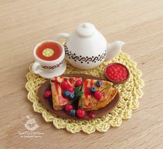 A set of miniature foods for Dollhouse and dolls.Pancakes with berries and tea.1:12 scale.Dollhouse food.Miniature food.Dollhouse. Pancakes with berries and tea, jam, cup and kettle made from polymer clay. Pancakes are glued to the plate. The napkin is tied with threads. Not