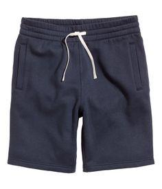 Azul oscuro. Pantalón corto en tejido sudadera con interior cepillado, largo hasta la rodilla. Cintura elástica y cordón de ajuste. Bolsillos al bies y un
