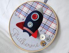 Quadro Porta Maternidade modelo Bastidor Foguetinho Espacial Confeccionado em tecido e feltro, decorado com botões plásticos e em madeira e personalizado com o nome do bebê. O quadro mede 30 cm de diâmetro e pode ser feito nas cores e estampas que desejar! R$ 180,00
