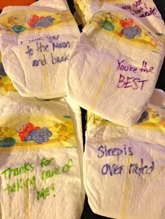 Baby Gift Basket - including diapers with funny and encouraging messages for the new parents. Put them in a bag to specify not to be used except for after midnight feedings :)