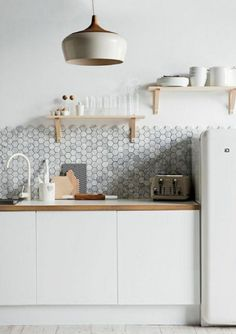 une jolie cuisine laquée blanche et mur en mosaique gris