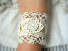 vintage fabric & lace cuff bracelets.They are a collage of vintage textiles. The base is vintage cotton or linen with added vintage laces both machine made and hand crocheted. strip of vintage cloth measuring tape, vintage mother of pearl buttons~ sheer palest pink floral rosette ~