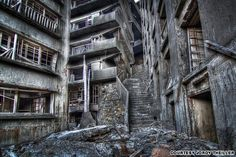 The infamous Stairway to Hell on Gunkanjima. Hashima Island, also known as Gunkanjima (meaning Battleship Island as the island resembles a warship) is a 60,000-square-meter cluster of concrete ruins in the sea by Nagasaki, Japan.  In the 1950s it was the bustling home of thousands of coal mine workers. Hashima Island has been abandoned since 1974 when the coal mines shut down.