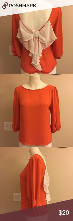 Fun top with bow on the back size small This top will have everyone doing a double take. So cute from behind with large ivory color bow. The top is a orange color and will be great for fall. Blouse is a polyester material. Sleeves are 3/4 and have elastic at the end. J&M clothing Tops Blouses