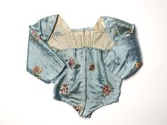 This woman's bodice is part of a gown made from sky-blue silk satin brocaded with a pattern of coloured sprigs of honeysuckle and carnations or gillyflowers. It is lined in linen. The dress, made in the 1770s, had been cut up before arriving at the museum for use by an amateur dramatic company.