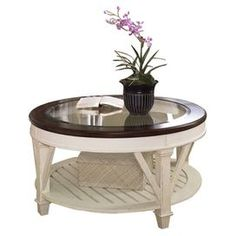 "Two-toned coffee table with a glass top and cantilevered moldings.   Product: Coffee tableConstruction Material: Deluxe pine solids, birch veneers and glassColor: Fruitwood and antique linen Features:  Band saw cabriole legs  Bottom shelf  Two-toned finish Dimensions: 20"" H x 40"" Diameter"