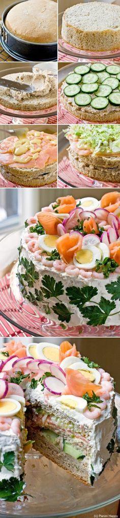 Herzhafte Torte, sieht toll aus und ist ein Partyrenner. Ursprünglich aus Schweden. Entrindetes Brot durchschneiden, mit Mayonnaise, weichem Gemüse, Käsescheiben, Schinkenscheiben füllen und garnieren. Wichtig: durchziehen lassen. Dann verbindet sich alles gut. Kann man gut vorbereiten.