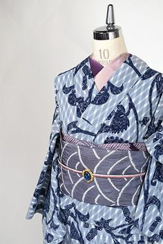 クールなグレーのアーガイルチェックに、ロマンチックなアラベスクパターンと、フォークロアな詩情ただようコケシと壺のモチーフが重ねられた注染レトロ浴衣です。