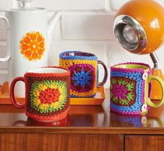 Need a crochet fix quick? Whip up a motif mug hug or two in a decidedly retro colour palette. You can adjust the length of the two fastening button loops so your cosy will fit comfortably around your chosen cup. Get a brew on. Crochet Coffee Cozy, Crochet Cozy, Crochet Gratis, Crochet Motif, Free Crochet, Crochet Patterns, Stitch Patterns, Knitting Patterns, Vintage Haken
