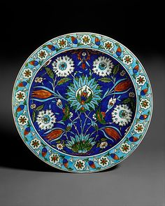 Dish   Joseph-Théodore Deck (French, 1823-1891)   Paris, France, circa 1870   Earthenware with underglaze and enamel polychrome decoration ('Persian' faience)   The decoration of this dish is derived from Turkish ceramics made in the town of Iznik between 15th-17th centuries. Although Deck borrowed Iznik colors and motifs, he did not make exact replicas of their designs. Instead he loosely adapted motifs, creating designs of his own invention   The Metropolitan Museum of Art, New York