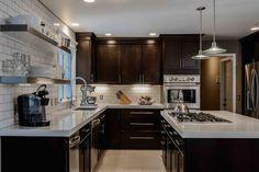 Dark Kitchen Cabinets with beige countertop beige floor brown wall cooktop dark wood cabinets dark wood drawers disk pendant light floating shelves kitchen cabinetry kitchens maple merillat open
