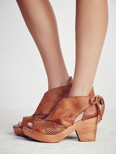 Revolver Clog | Open toe leather clogs featuring a perforated design on the sides and adjustable ties in back. Grainy wooden heels with padded insoles and treaded rubber soles.