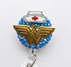 This is a clear lucite retractable badge reel backing, along with a handy swivel alligator clip or a belt/slide clip SEE DROP DOWN BOX FOR OPTIONS. A metal image of Wonder Womans iconic symbol adorns this reel along with a Nurses cap which has been embellished with red Swavorski