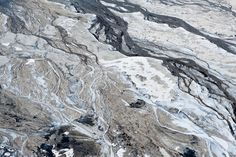 Alberta Tar 'Ponds' in winter.. Frozen water (which flows with the natural tar and oil reserves of planet) - freezes and the oil does not hence the effective photographic result.