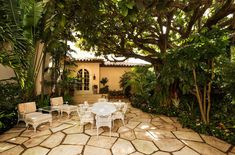 JFK's Winter White House Sells for $31 Million - Shady Seat - A shaded outdoor seating area is situated beneath a thicket of palms and banyon trees on one of the home's stone terraces.