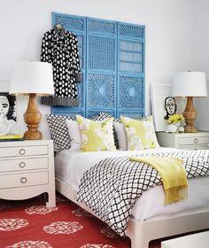 Cabeceira de cama feita com um biombo de vime encostado na parede.