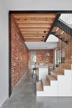 Mark St, Fitzroy North Living room, stair, under stair joinery, cable wire handrail, concrete floors, kitchen, exposed brick wall, exposed timber joists