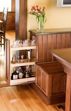 Neat idea to incorporate pull-out cabinet in breakfast nook. The bench also flips up for more storage. Crown Point Cabinetry