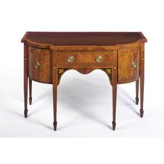 A GEORGE III EBONY-INLAID MAHOGANY SMALL SIDEBOARD, LATE 18TH CENTURY the frieze drawer flanked by a deep drawer and a cupboard.