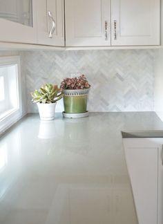White cabinets with marble herringbone backsplash and sage green quartz countertops