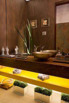 parede marrom, bancada madeira escura, prateleira laca amarela, toque de verde nas plantas