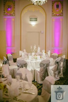 Vibrant purple lighting adds a modern touch to this elegant ballroom.