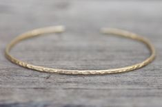"""Au Magic"""" A solid 14kt yellow gold cuff bracelet, dainty, understated, hammered, with rounded ends for a comfortable fit. 100% eco-friendly recycled gold. Default size fits between a size 6.25 - 6.75 wrist. This is crafted in 14 gauge, making for a thin cuff that is somewhat malleable. Just"""