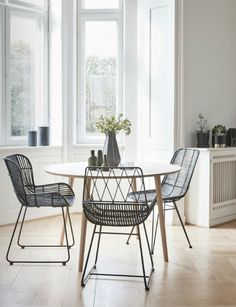 Bright dining room with a wooden dining table and black dining chairs from Hübsch.