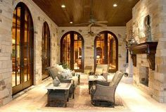 Mediterranean Porch with French doors, Built-in bookshelf, travertine tile floors, Ceiling fan, stone fireplace