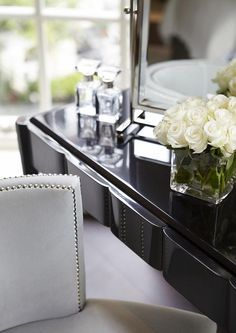Chic dressing room boasts glossy black lacquer make up vanity topped with a pivot mirror alongside a gray velvet nailhead stool.
