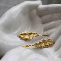 A pair of delicate gold oak leaf hair slides.These hair pins make the perfect addition to any hairstyle. Perfect for pixie crops, long tousled waves or dressing up a chic chignon. The hair grips will be sent in an organic cotton Little Nell drawstring bag, or can br gift wrapped if purchased as a present. Gift boxes are in kraft brown, tied with twine and a black gift tag. They make lovely gifts for bridesmaids or friends who like something a bit different.Gold toned brass.The grip is 5.3cm…