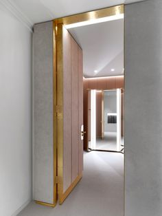 A doorway framed with the gold-coloured metal conceals a fitting room lined with pink-coloured panels in this London boutique.