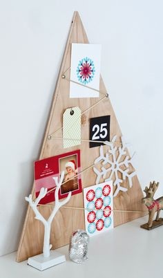 Simple and stylish, these DIY Christmas decorations and craft ideas—including this adorable wooden Christmas tree holiday card display—can be used to add warmth and charm to your home this holiday season.