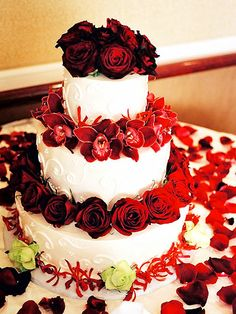 Rose and Orchid Covered:   A divine dessert and floral elegance combine to create a cake that is nearly too beautiful to eat. Red and green roses and two types of red orchids decorate the tiers.   -- Photographer Mark Hopkins; Floral designer Amina Marechal