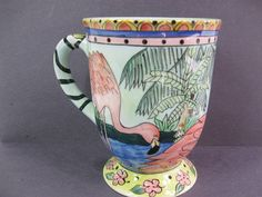 Flamingo coffee mug beautifully hand-painted with tropical design. Possibly scene from Long Beach Island, NJ. The cup stands 5 tall and holds 12oz.