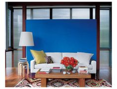 With a brilliant blue feature wall, this Long Island living room always appears sunny.