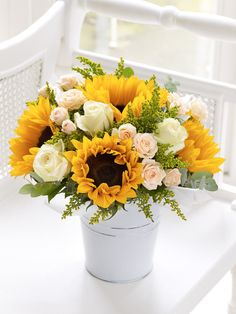 Fairtrade Sunflower and Rose Pail - Interflora Featuring 4 yellow sunflowers, 3 peach spray roses and 3 cream roses with solidago and eucalyptus, presented in a white rustic pail.