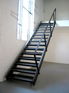 Custom blackened steel staircase with diamond plate treads by Face Design + Fabrication
