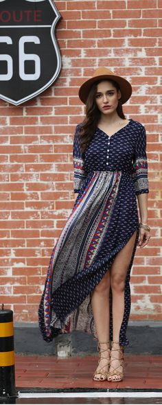 A navy maxi dress with an allover print, a five-button front, an elasticized waist that can be paired with a belt to enhance your charm , slit skirt, and 1/2 sleeves with elasticized cuffs.