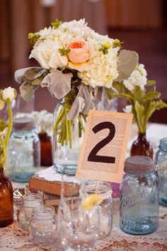 a clustering of mason jars used as centerpiece decor, some propped on vintage books and used as vases