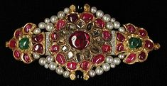 Centerpiece from an Armlet later made into a Brooch. 18th–19th, Northern India: gold, inset with rubies, emeralds and colorless sapphires; with later pearls, diamonds and onyx. The Metropolitan Museum of Art.